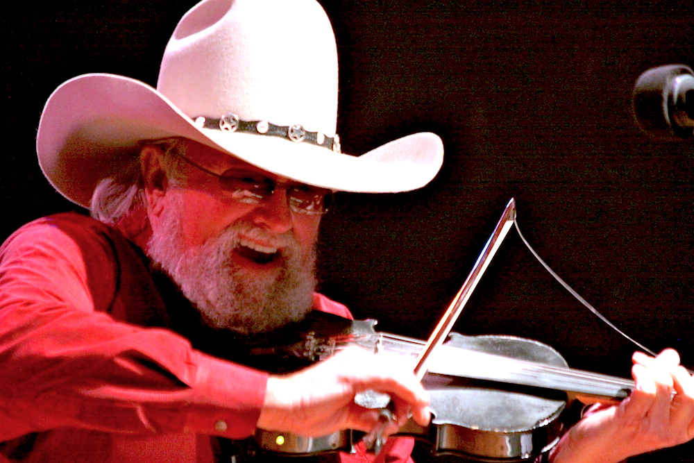 Charlie Daniels plays fiddle on stage.
