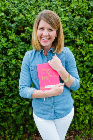 Emily Ley posing with her new book, Grace Not Perfection.