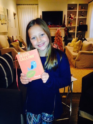 Kari Kampakis' daughter with a copy of Jesus Calling 365 Devotions for Kids.