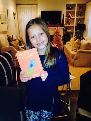 Kari Kampakis' daughter with a copy of Jesus Calling 365 Devotions for Kids.