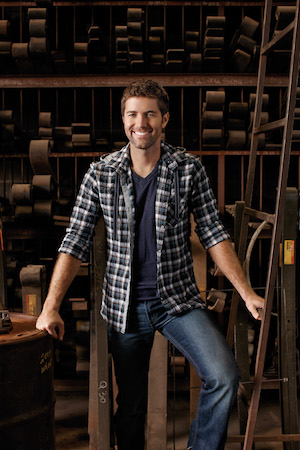 Josh Turner smiles and poses in a warehouse.