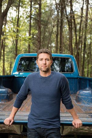 Josh Turner standing by his blue truck.