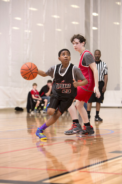 A boy with the Upward program dribbles a basketball.