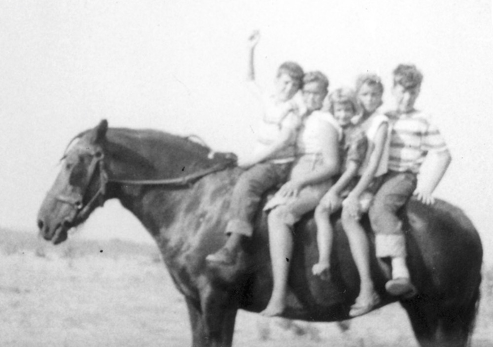Edie Sundby as a child on a horse with her siblings.