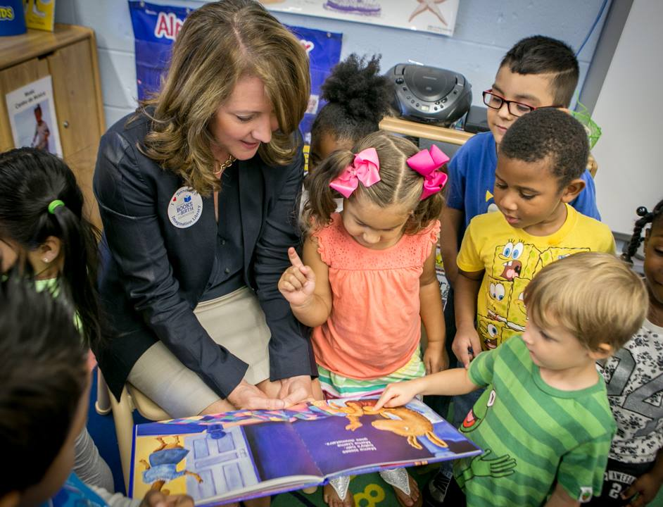 First Lady Crissy Haslam reading a book to children.