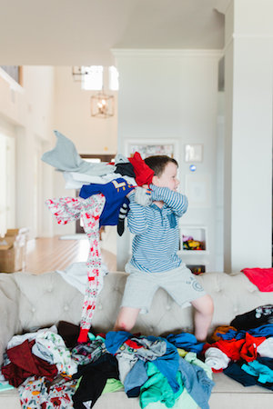 Emily Ley's son throwing clothes while standing on their couch.