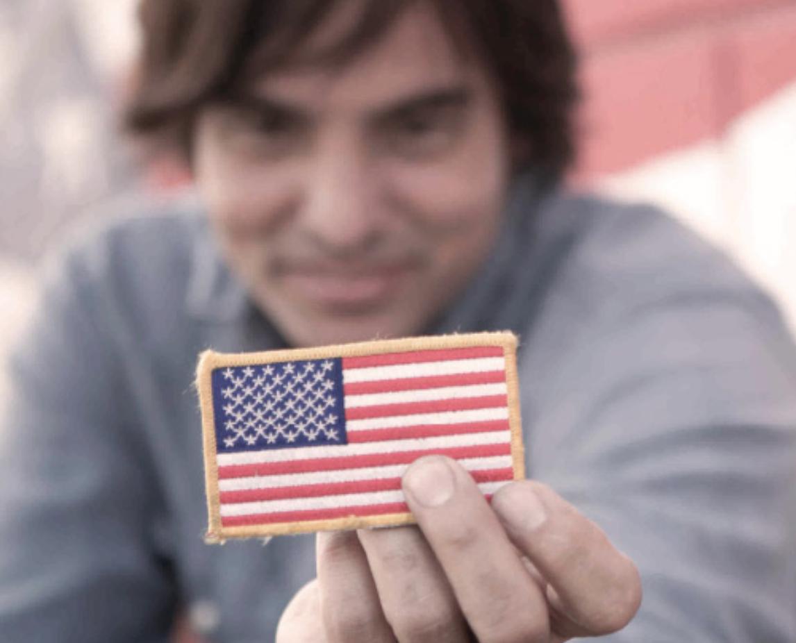 Keni Thomas holding American flag patch