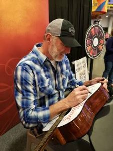 Darryl Worley signing the Jesus Calling guitar at CMA Fest 2019